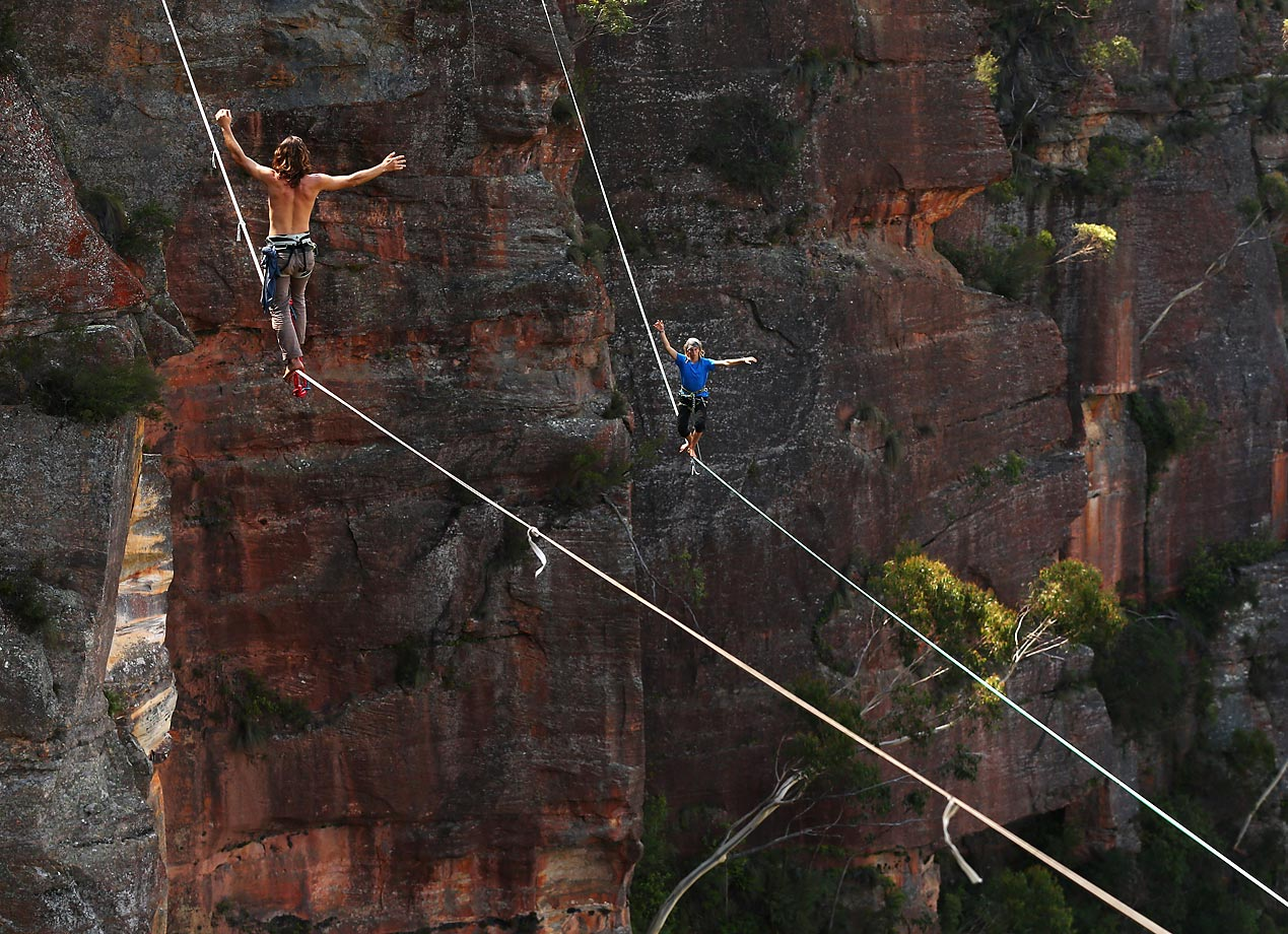 Guilherme Lopes of Brazil (left) and Joseph Huard of Canada walk across 60- and 90-meter highlines, respectively, rigged between cliffs at Corroboree Walls in Mount Victoria in Australia.
