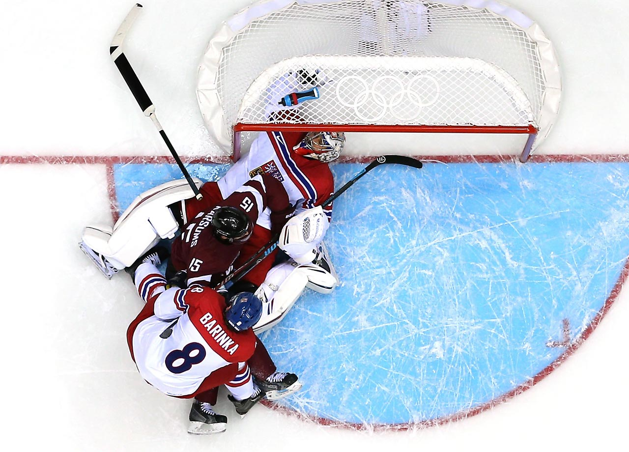 Martins Karsums of Latvia gets tangled up with Michal Barinka and Ondrej Pavelec of the Czech Republic.