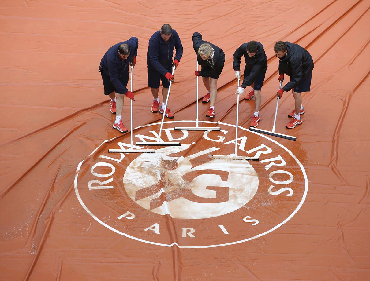Workers remove water from the rain tarp at the French Open.  Wait, isn't that the purpose of a rain tarp?