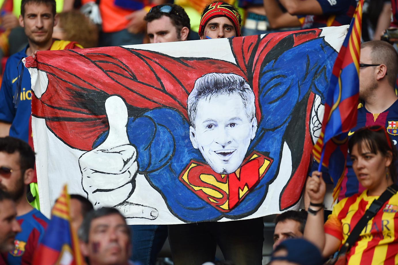 FC Barcelona fans display a poster of Lionel Messi as Superman before the UEFA Champions League Final between Juventus and FC Barcelona in Berlin on June 6.