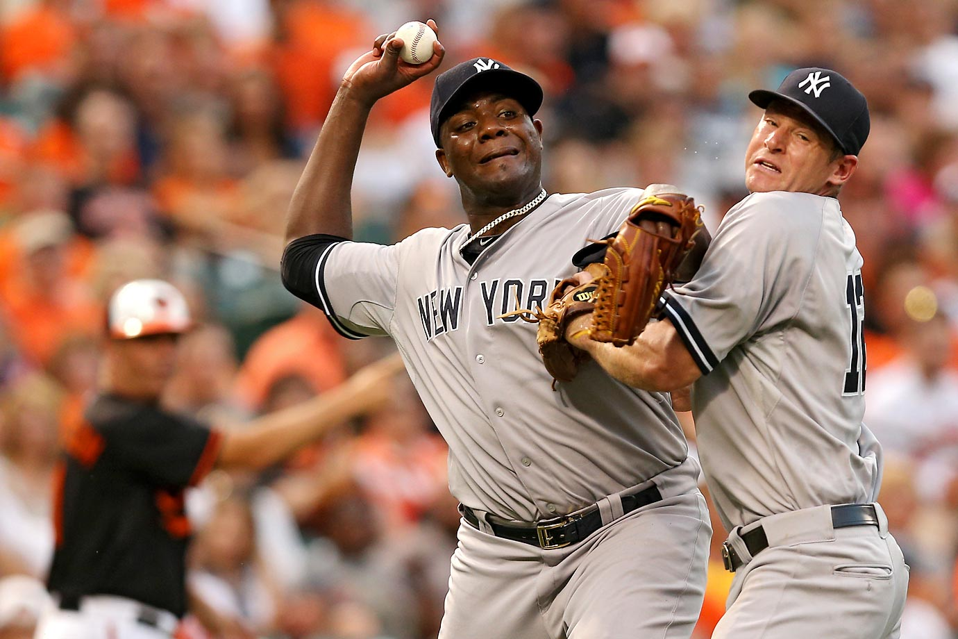 Michael Pineda of the New York Yankees collides with Chase Headley as he tries to throw out Jimmy Paredes of the Baltimore Orioles.