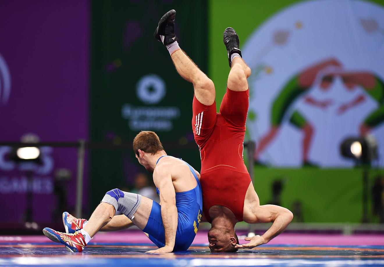 Istvan Levai (red) of Slovakia and Denys Dem'Yankov (blue) of Ukraine compete in the 66kg Greco Roman bronze final at the Baku 2015 European Games.