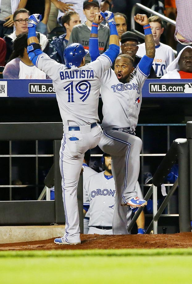 Jose Bautista and Jose Reyes of the Toronto Blue Jays celebrate after a game-tying home run in the ninth inning against the New York Mets.