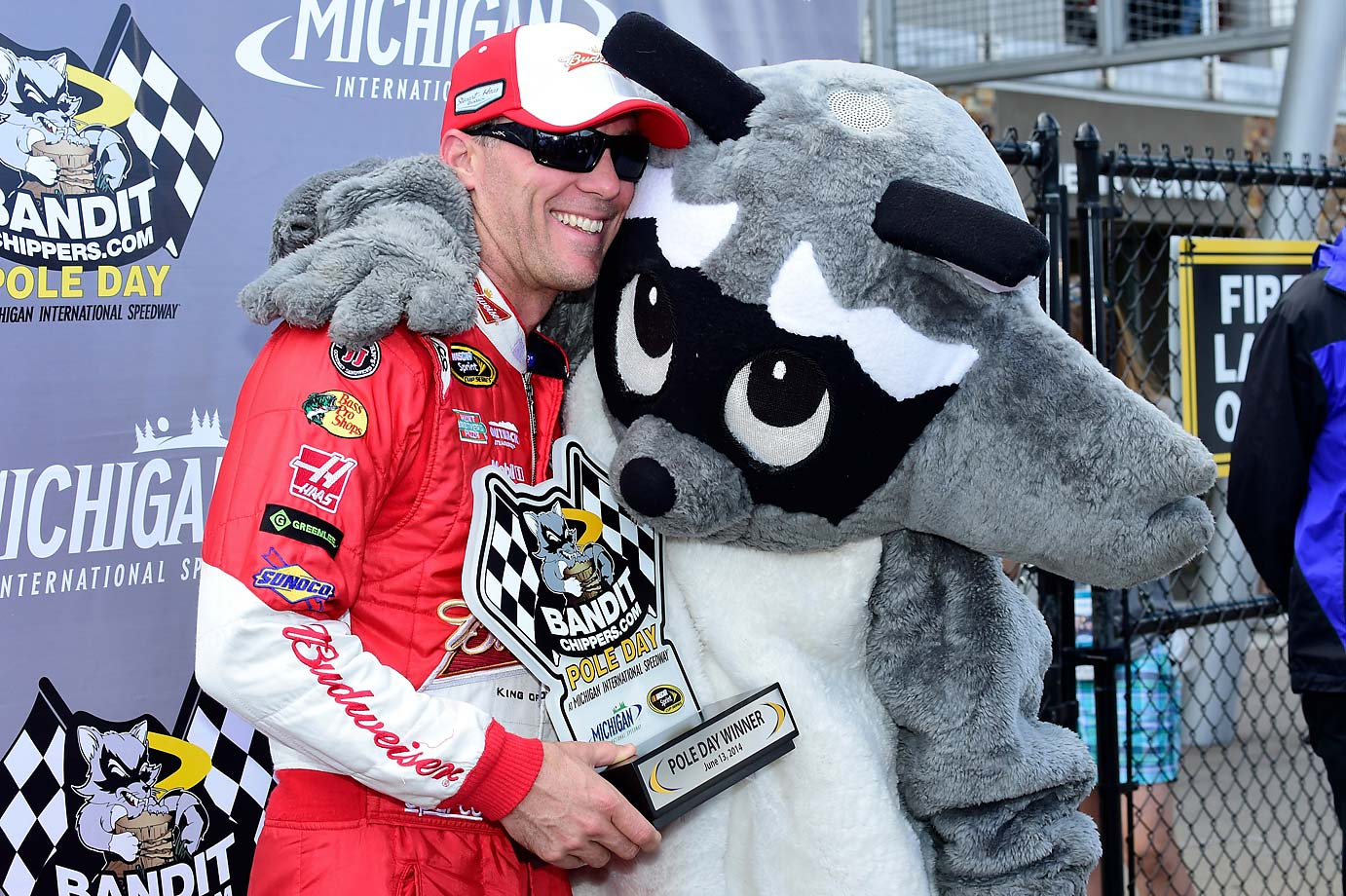 Kevin Harvick gets a hug from Bandit after winning the Pole Award at Michigan International Speedway.