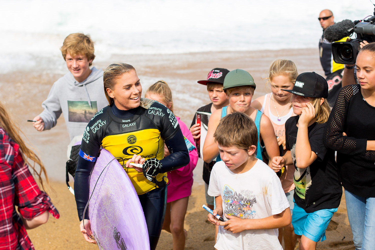 Dimity Stoyle walks off the beach surrounded by fans in Bells Beach, Australia after winning her heat with a 15.76 mark, the highest total of the day.