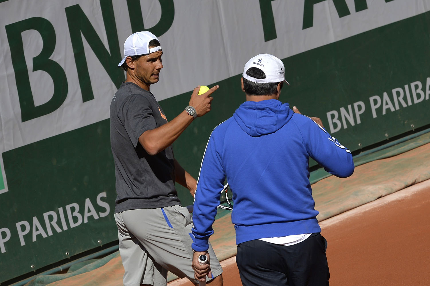 Spain's Rafael Nadal (L) speaks with his trainer during a training session at the Roland Garros stadium in Paris on May 22, 2014, ahead of the 2014 French Open.