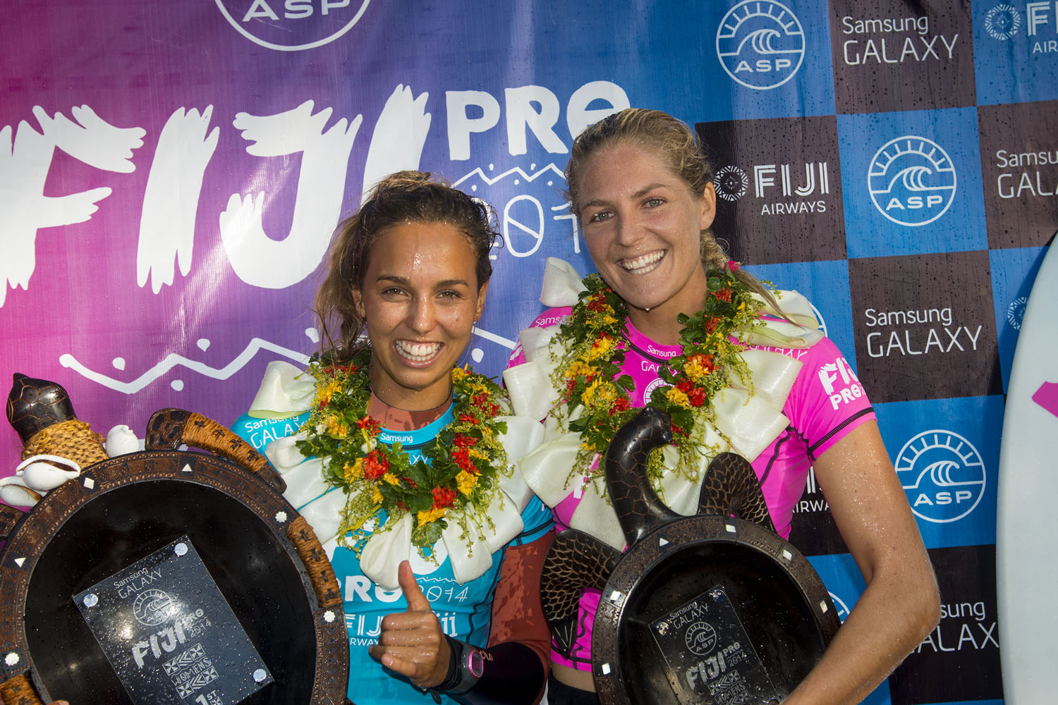 Sally Fitzgibbons (L) stands with runner-up Stephanie Gilmore (R) during the trophy ceremony in Tavarua, Fiji.