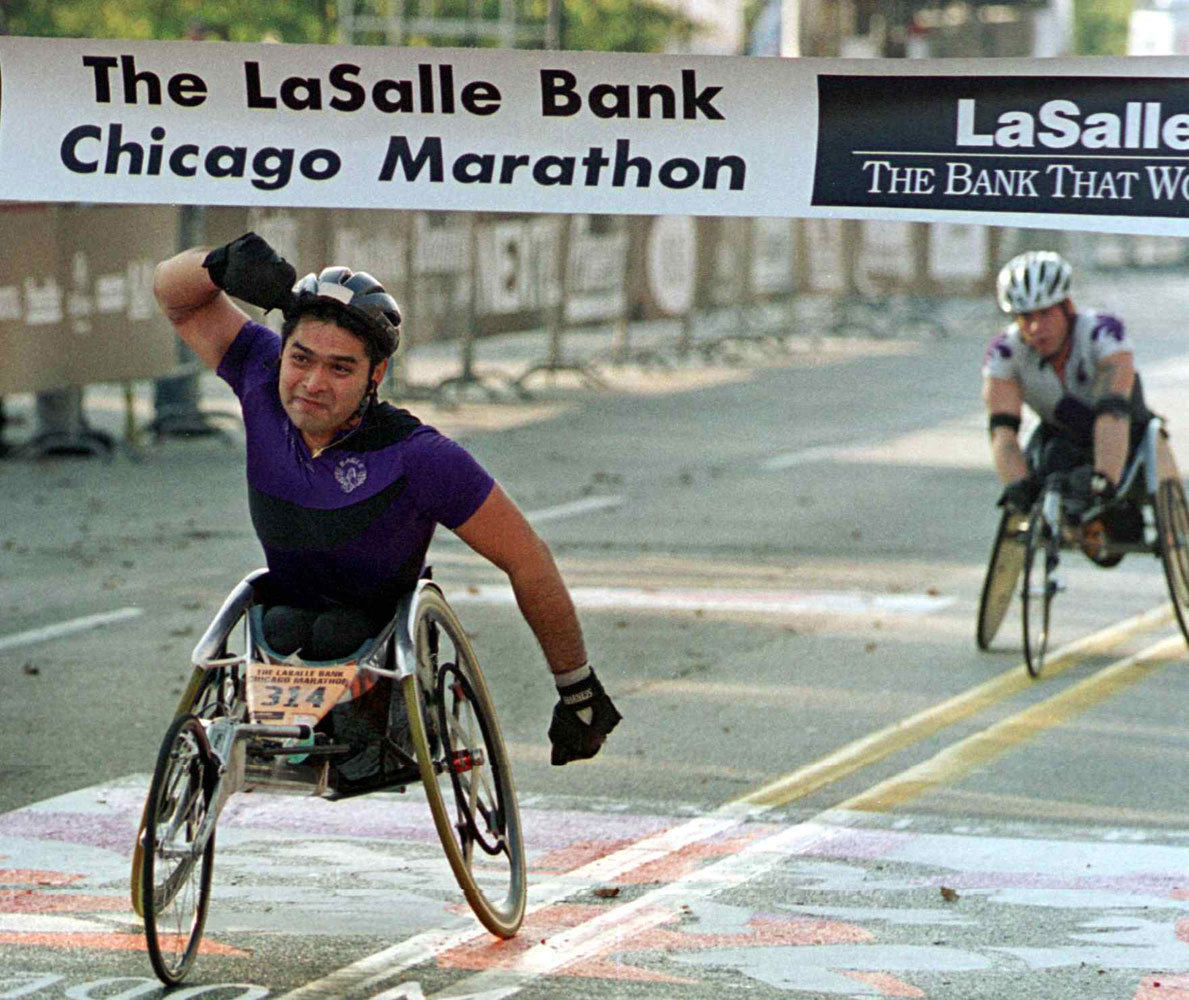 Tony Iniguez (L) pumps his fist as he crosses the finish line to win the wheelchair division of the Chicago Marathon in October 2000.