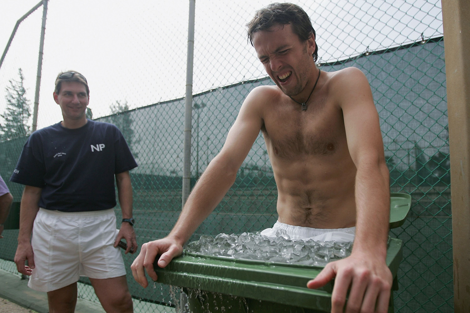 "Lee Childs, who was once hailed as ""the future of British tennis,"" eases into an ice bath as his coach looks on, watching Childs suffer."