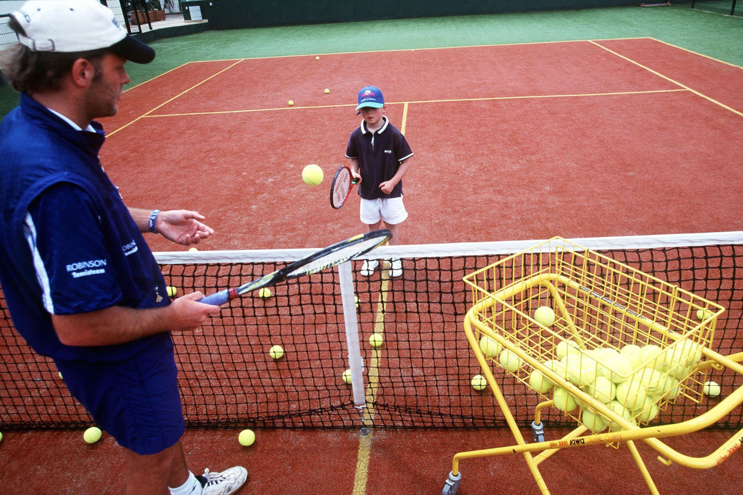 A young tennis player practicing the fundamentals of tennis with his coach at center court.