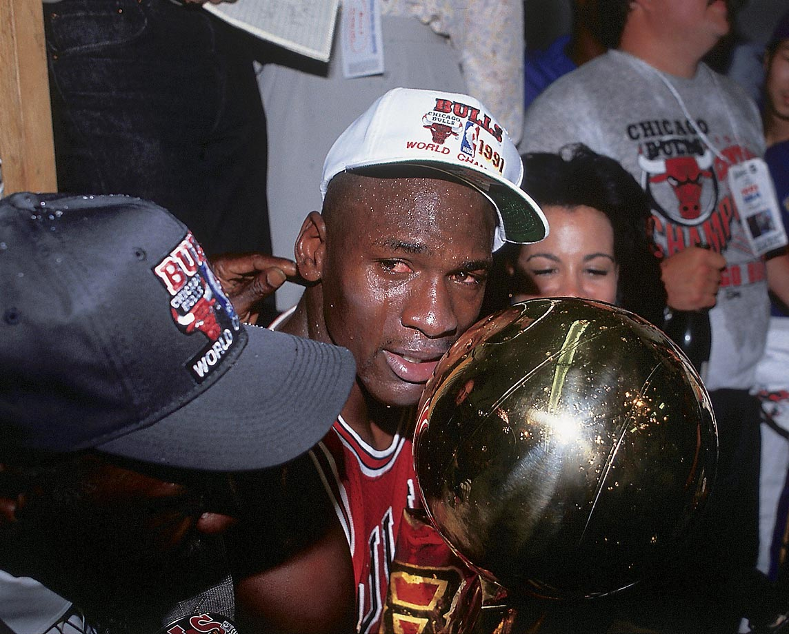 With his parents at his side, Michael Jordan holds the Chicago Bulls' first-ever championship trophy after defeating the Los Angeles Lakers in five games.