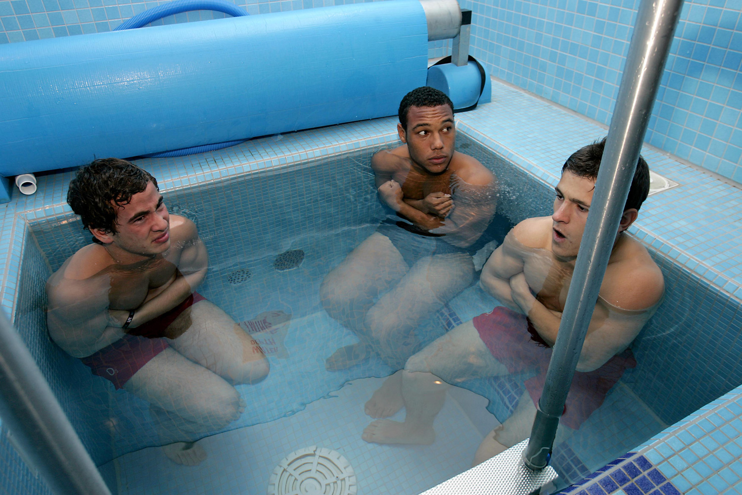 Players from the England Rugby Junior National Academy sit in the cold ice pool during a hydrotherapy session.