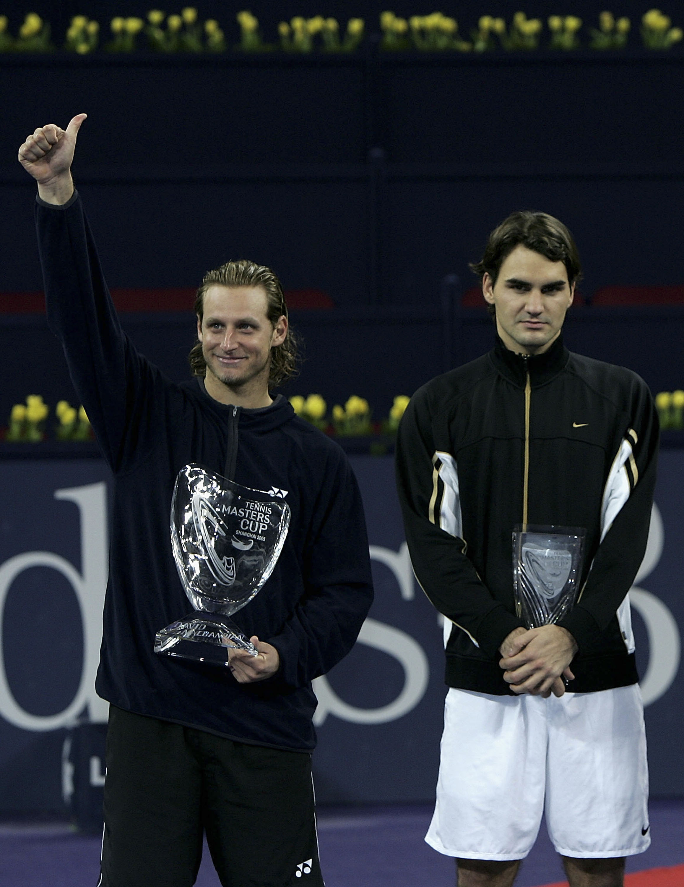 Nalbandian holds the trophy after his five set victory over Federer as the Swiss looks on.
