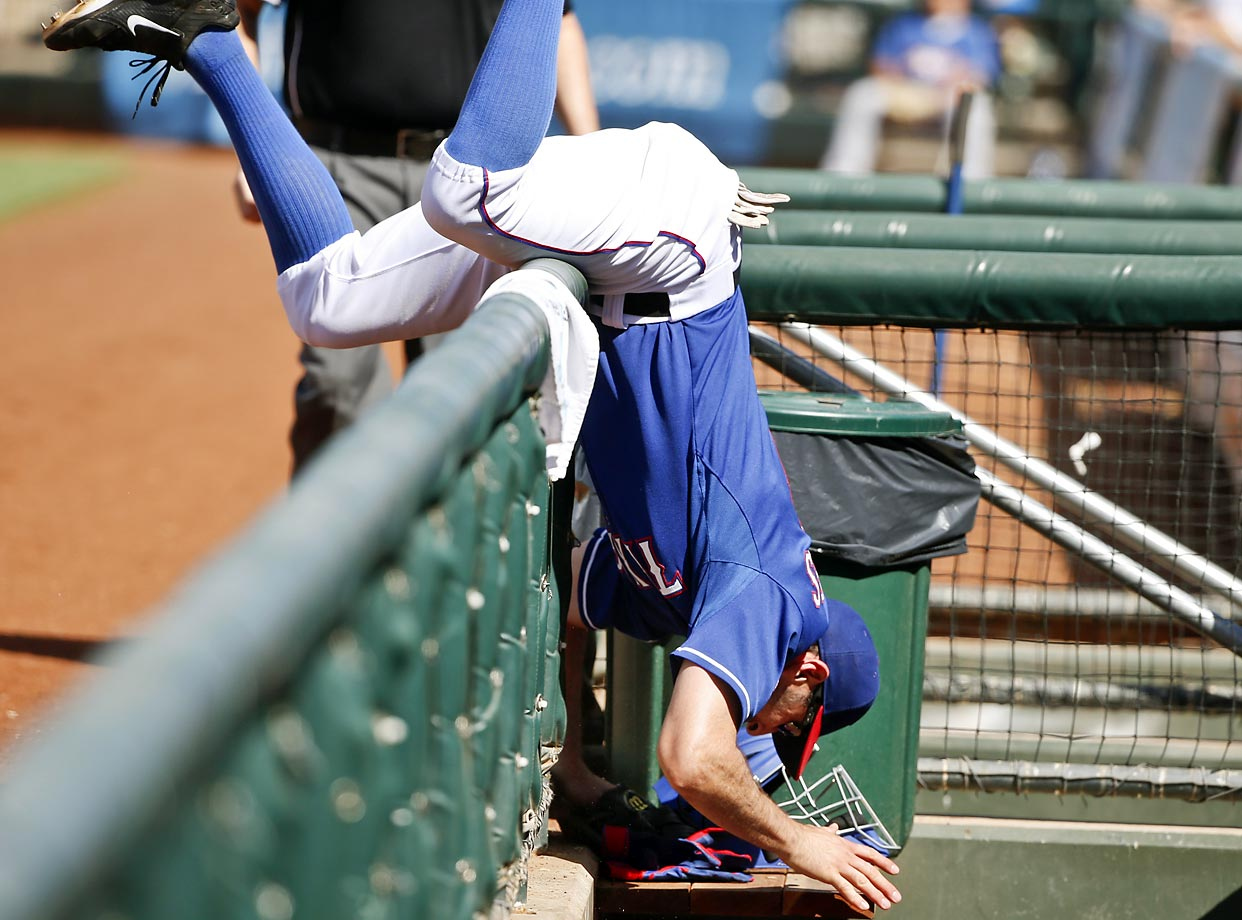 Texas Rangers first baseman Adam Rosales tumbles over the dugout railing while chasing a foul ball during a Spring Training game in Surprise, Ariz.