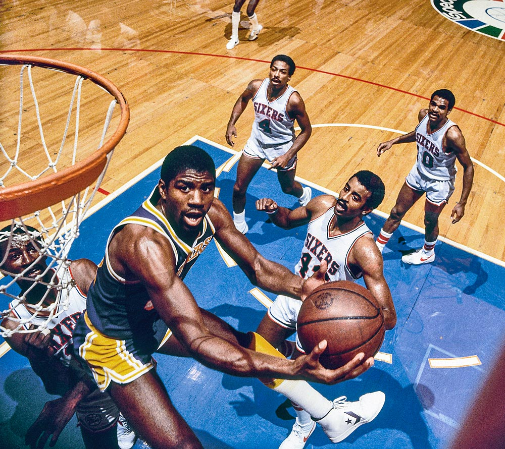 Magic Johnson attacks the hoop against the Sixers. Johnson fell just short of averaging a triple-double in the six-game series, with 16.2 points, 10.8 rebounds and 8 assists per game and winning MVP honors.