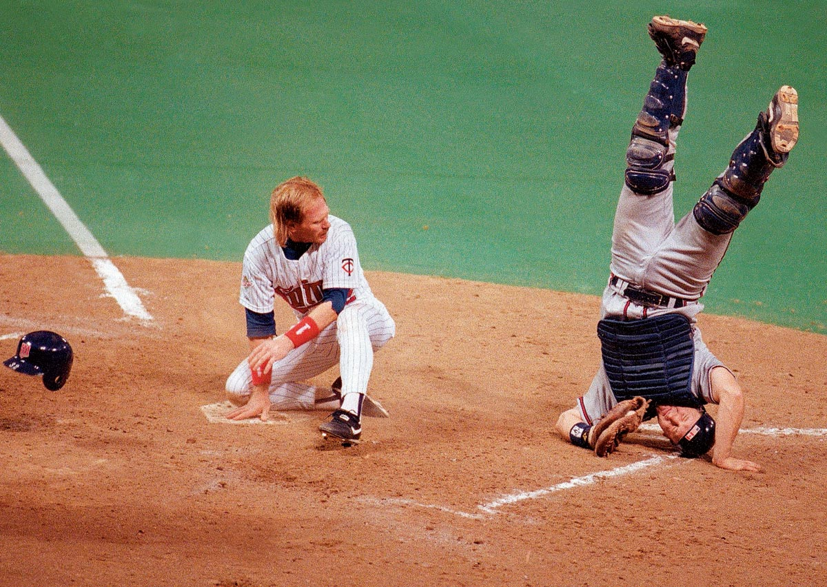 World Series Game 1, Oct. 19, 1991 | Atlanta Braves catcher Greg Olson goes head over heels after tagging Minnesota left fielder Dan Gladden out at home during Game 1 of the 1991 World Series. The Twins would win Game 1, 5-2, and go on to win the Series in seven games.