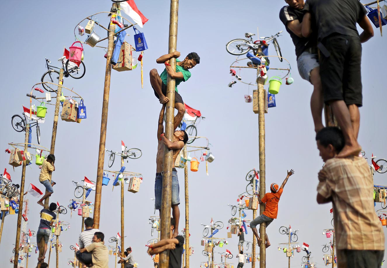 Participants struggle to reach the prizes during a greased-pole climbing competition in Jakarta, Indonesia.  The country is celebrating the 69th anniversary of its independence from the Dutch colonial rule.
