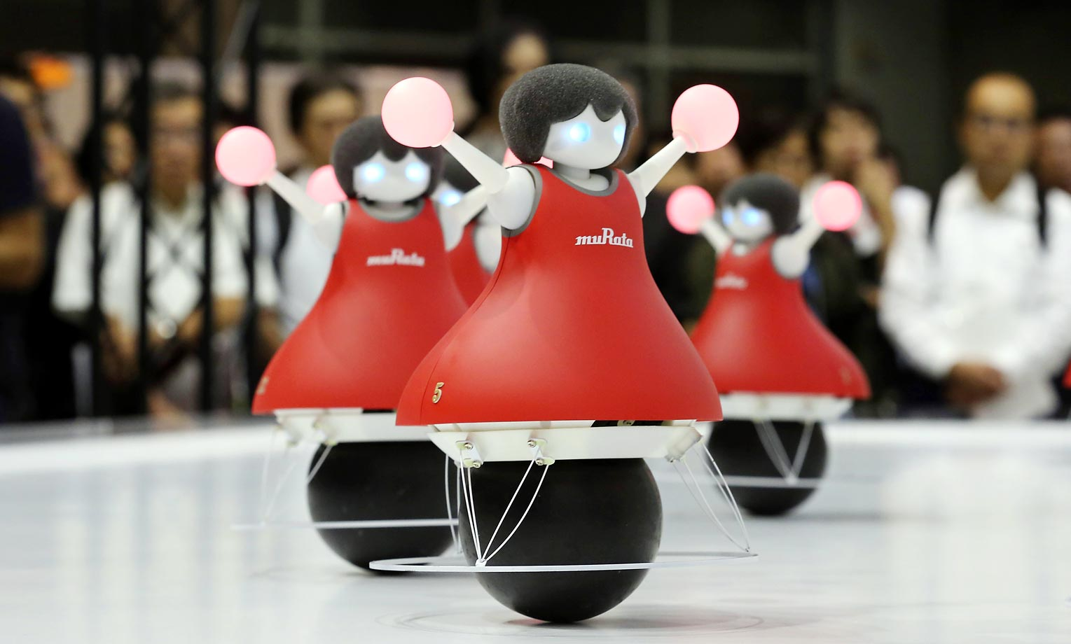 Robot cheerleaders, with color-changing pom-poms, perform synchronized dancing during the annual CEATEC Japan advanced technologies show.