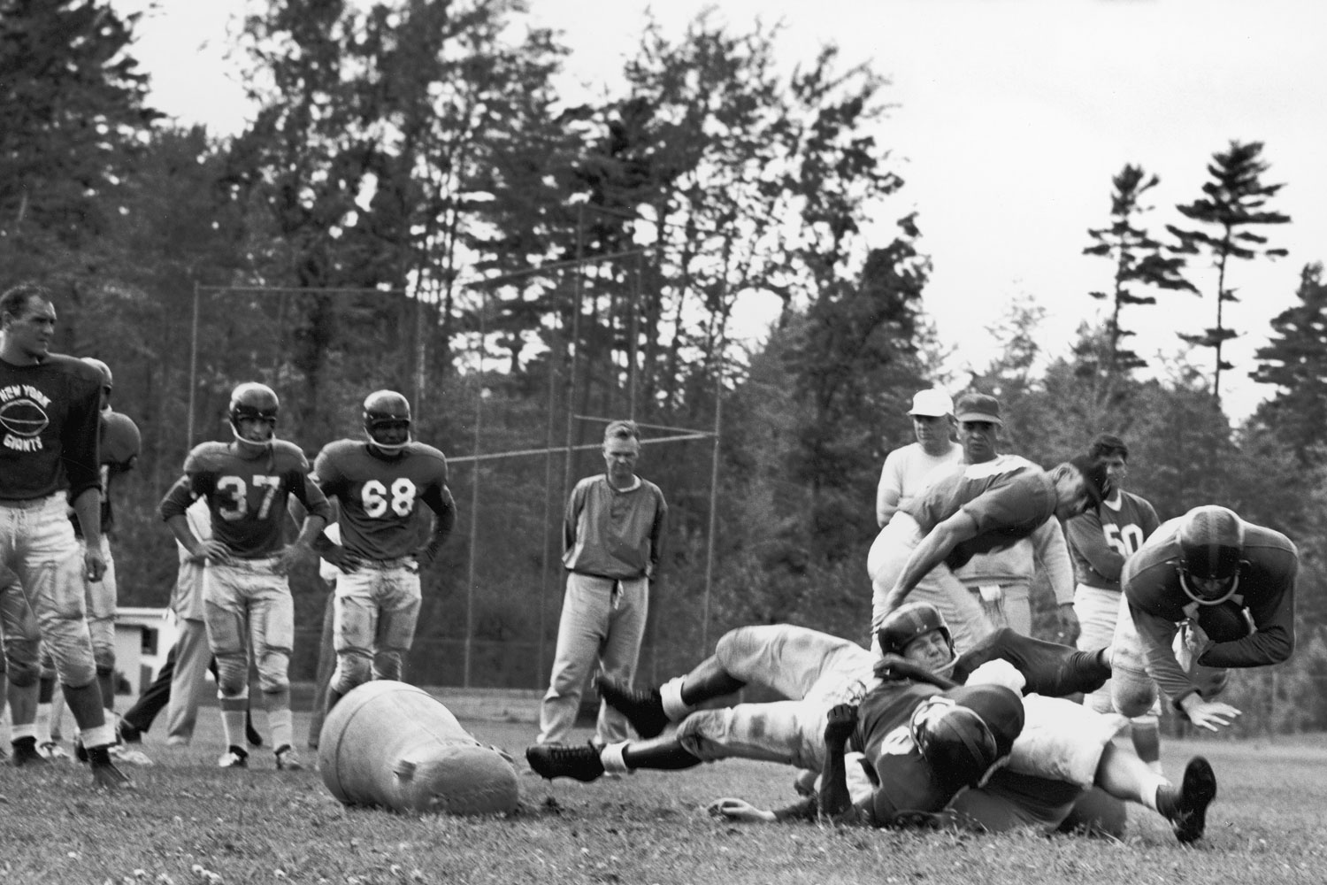 New York Giants players participate in training camp in the 1950's as offensive coordinator Vince Lombardi looks on. Giants co-owner Wellington Mara stands in the background.