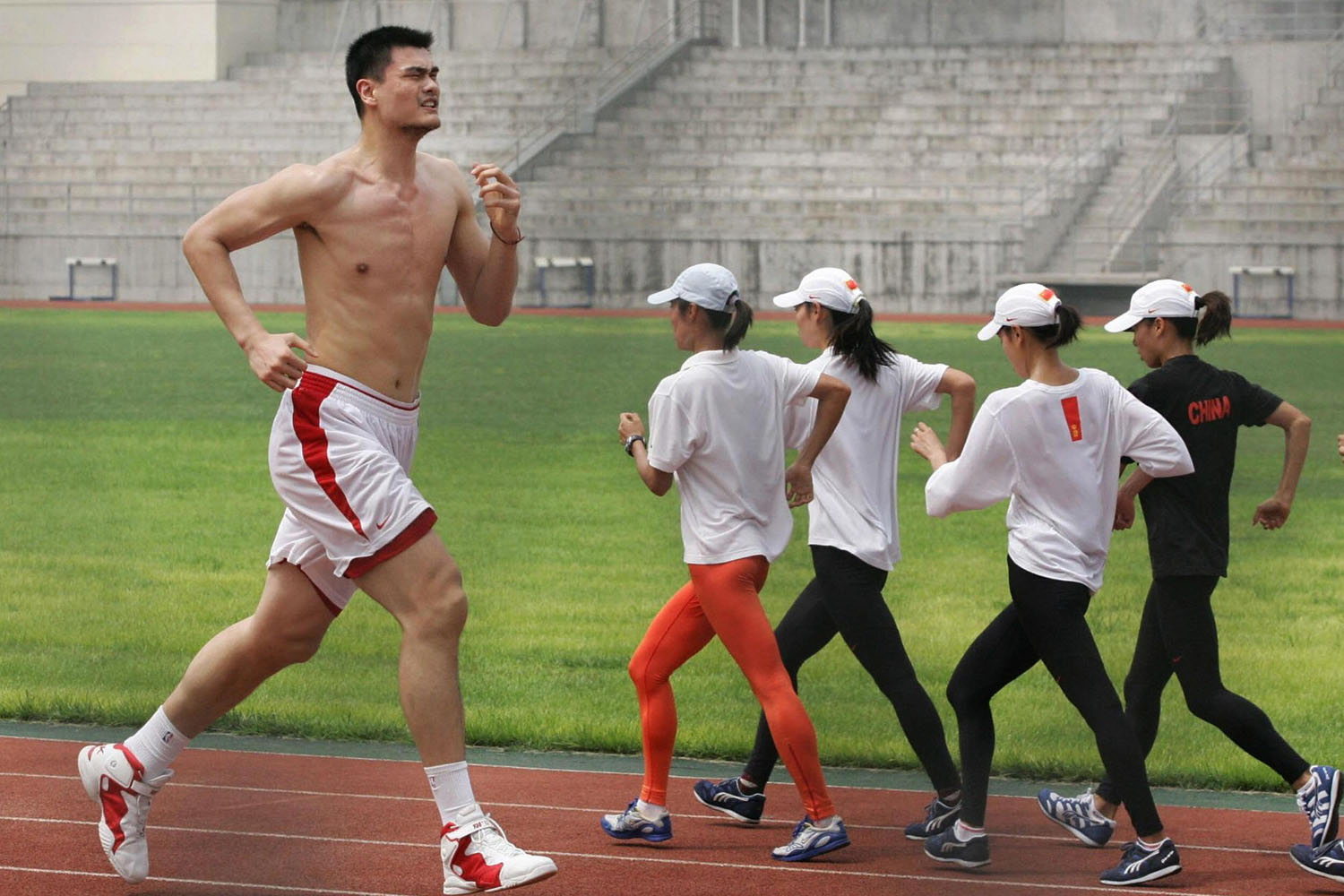 Yao Ming runs around a track during a training session in Beijing for the upcoming World Basketball Championships which begin in Japan in 2006.