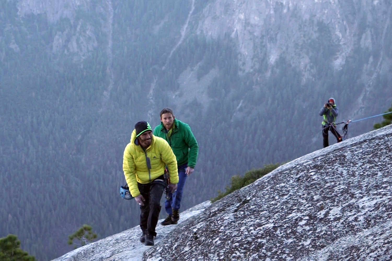 Kevin Jorgeson (in yellow) and Tommy Caldwell (in green) hiking up the summit towards the crowd.