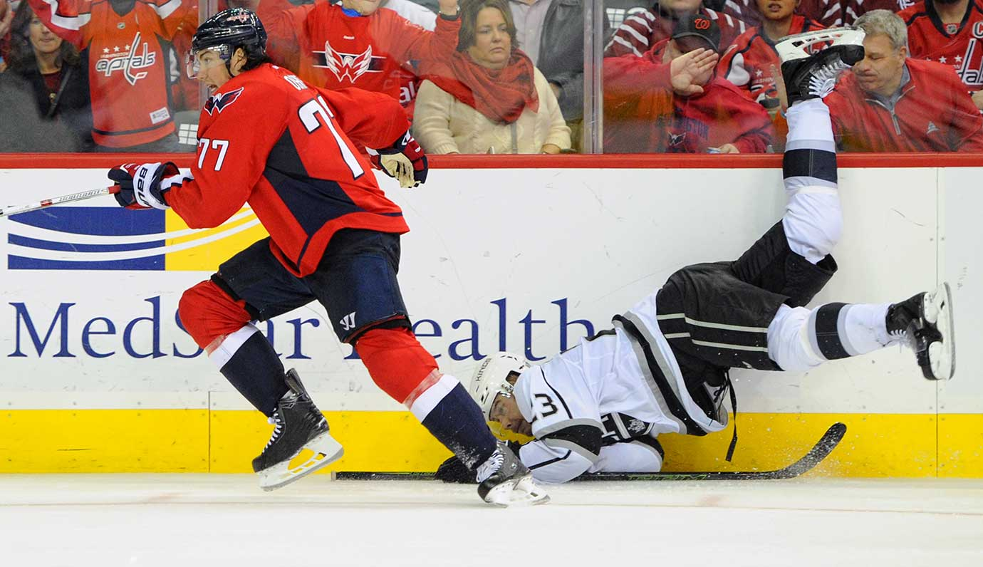 Washington Capitals right wing T.J. Oshie dumps Los Angeles Kings right wing Dustin Brown .
