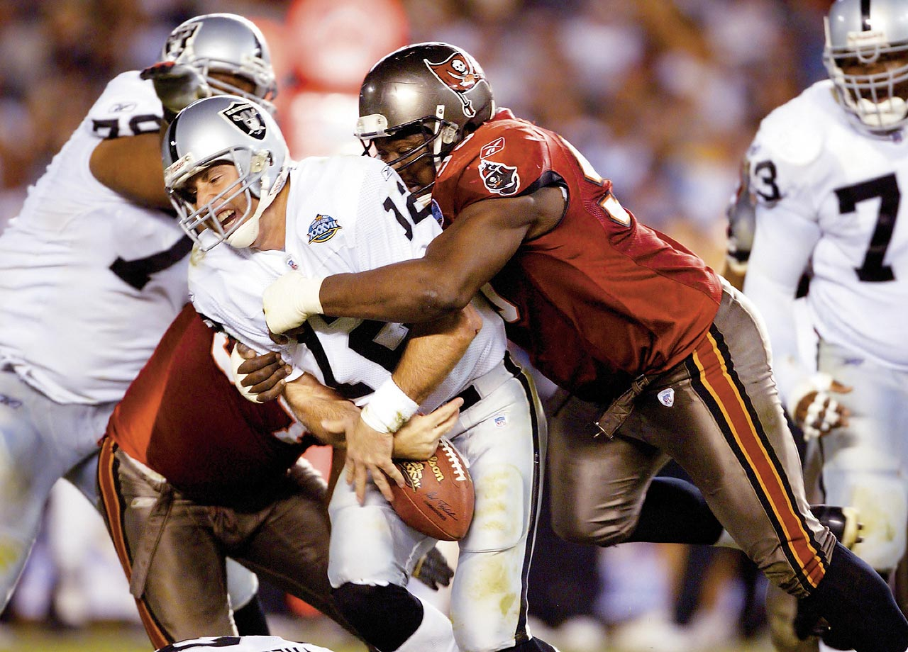 Tampa Bay defensive tackle Warren Sapp brings down Oakland quarterback Rich Gannon and jars the ball free for a fumble. Although the Raiders recovered the fumble, the Buccaneers' defense controlled the game, scoring three touchdowns on interception returns. Those touchdowns helped Tampa Bay easily prevail 48-21.