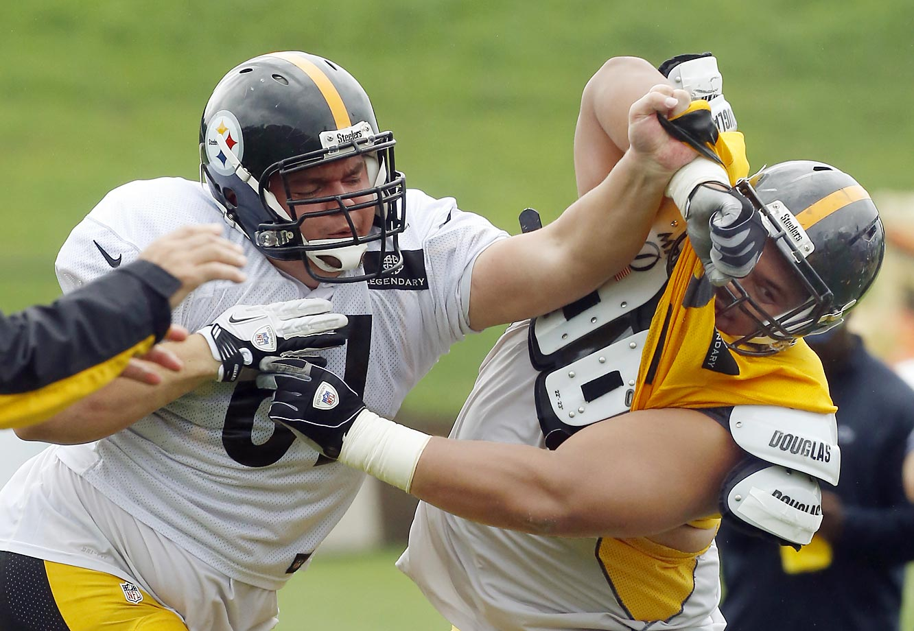 NFL training camps are well underway. In Latrobe, Pa., Pittsburgh Steelers center Chris Elkins (left) tries his hand at blocking defensive tackle Hebron Fangupo (92) during a practice drill.