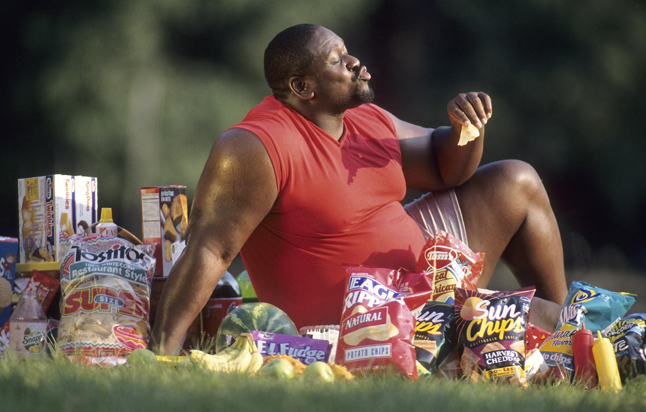 "Dallas Cowboys lineman Nate Newton is on the ""eat everything"" diet as he samples from every snack imaginable during a 1995 SI photo shoot."