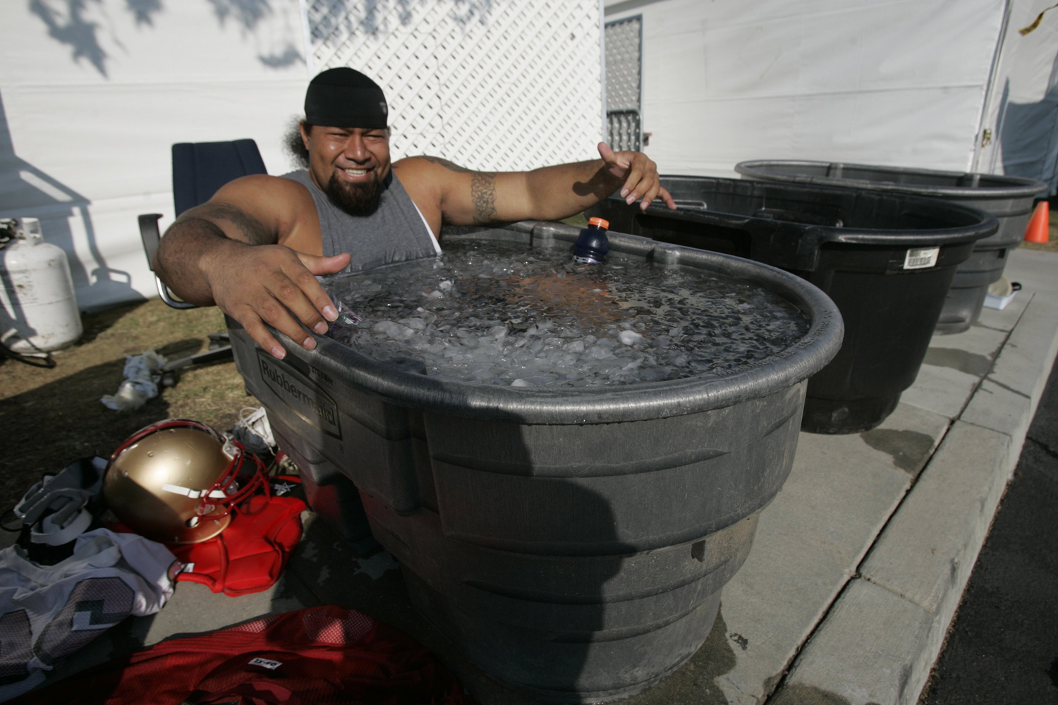 "Former defensive tackle Isa'ako ""Isaac"" Sopoaga endures an ice bath after practice at the San Francisco 49ers' training camp in July 2008."