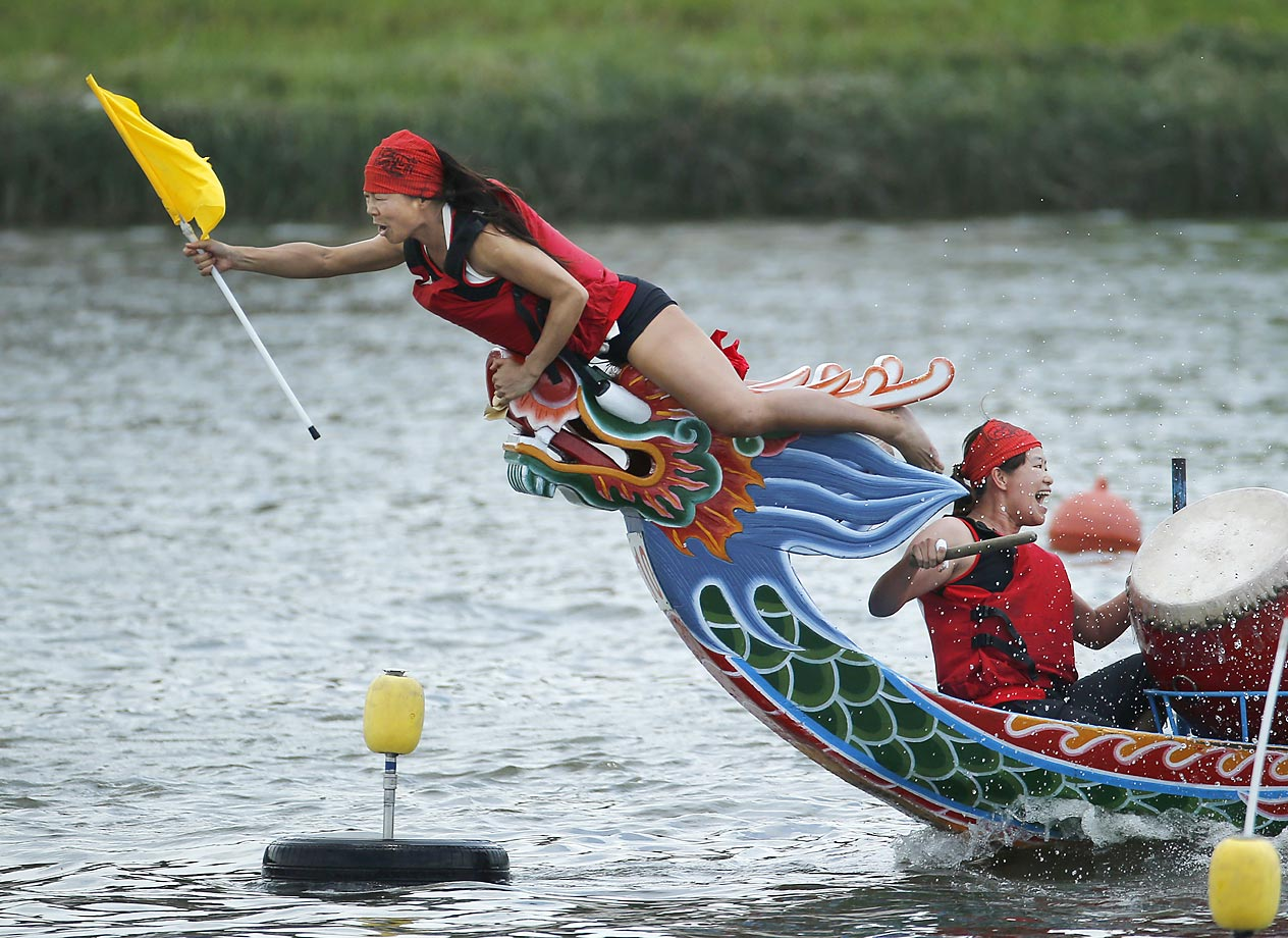 The boat captain grabs her finish line flag during the Chinese Dragon Boat race in Taipei.