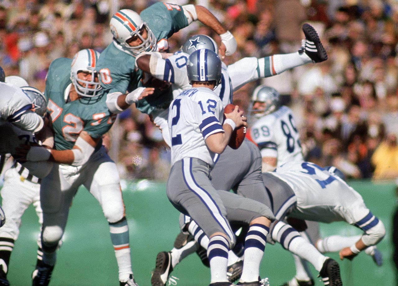 Roger Staubach sets to pass against the Miami Dolphins. Although the Dallas Cowboys quarterback was outdueled by the Dolphins' Bob Griese in passing yards, Staubach claimed the more important victory, snapping the Cowboys' reputation for being unable to win important playoff games. Staubach was named Super Bowl MVP after completing 12 of 19 passes for 119 yards and two touchdowns in the 24-3 win.
