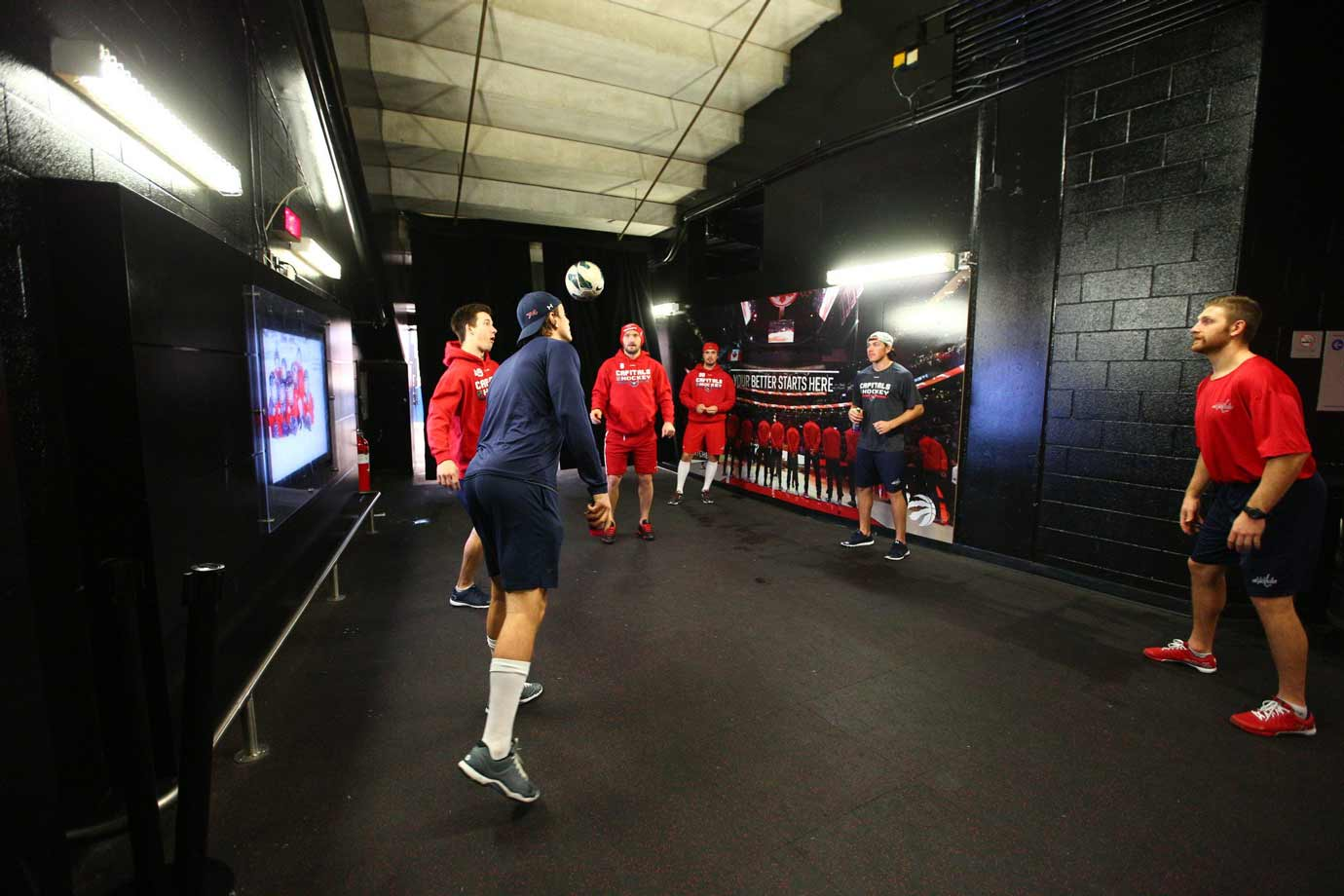 Some of the Caps warm up in the hallway outside their locker room by kicking a soccer ball around.
