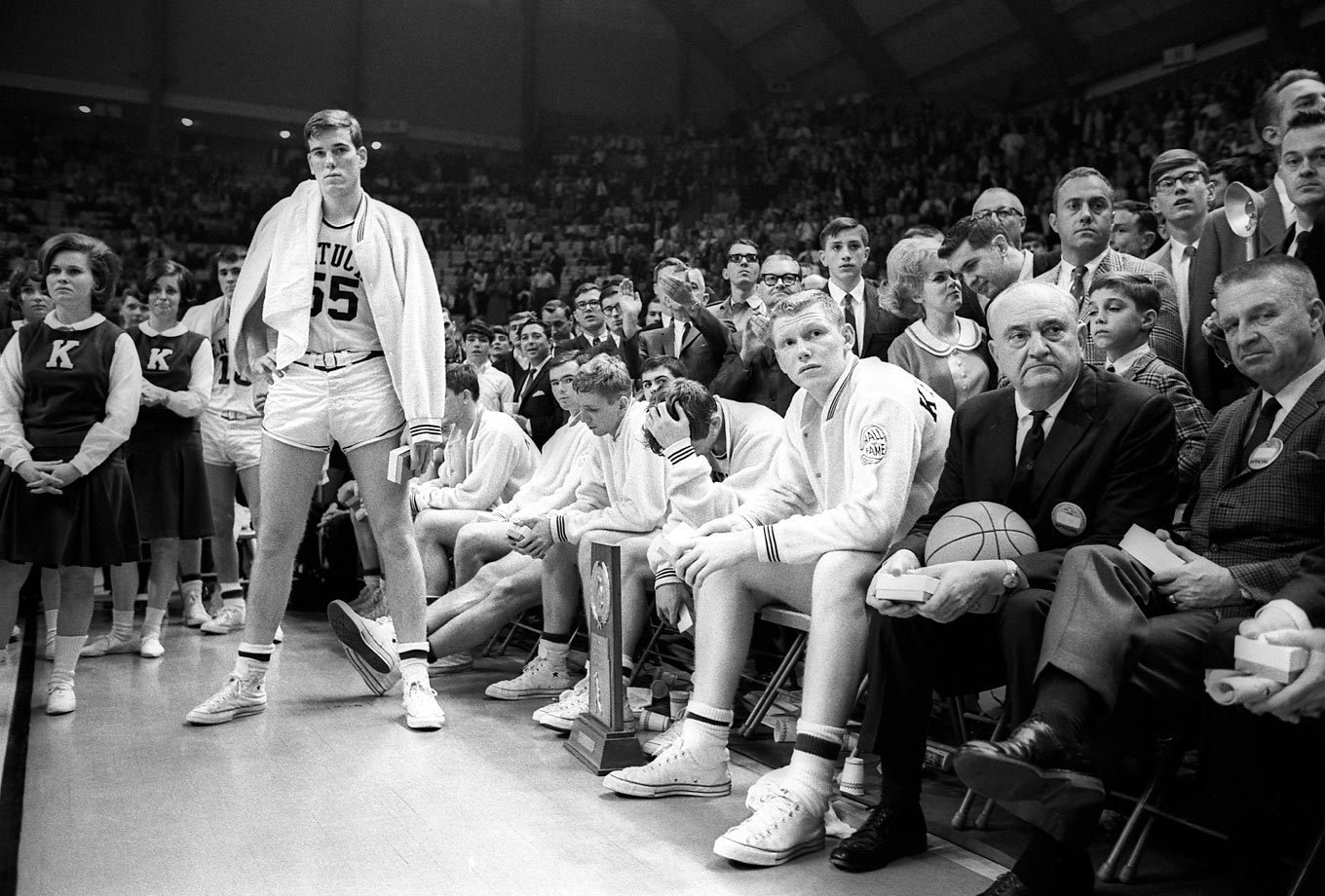 Kentucky coach Adolph Rupp (with basketball) and his players watch as Texas Western receives the championship trophy. Kentucky lost 72-65 after Texas Western's Bobby Joe Hill had successive steals to turn the game around.