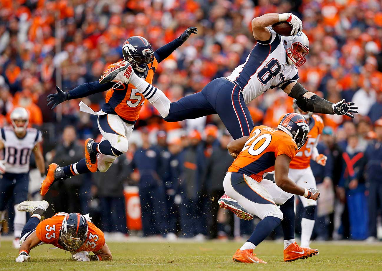 Rob Gronkowski is tackled by  Josh Bush #20,  Shiloh Keo and  Danny Trevathan in the fourth quarter.  Images)