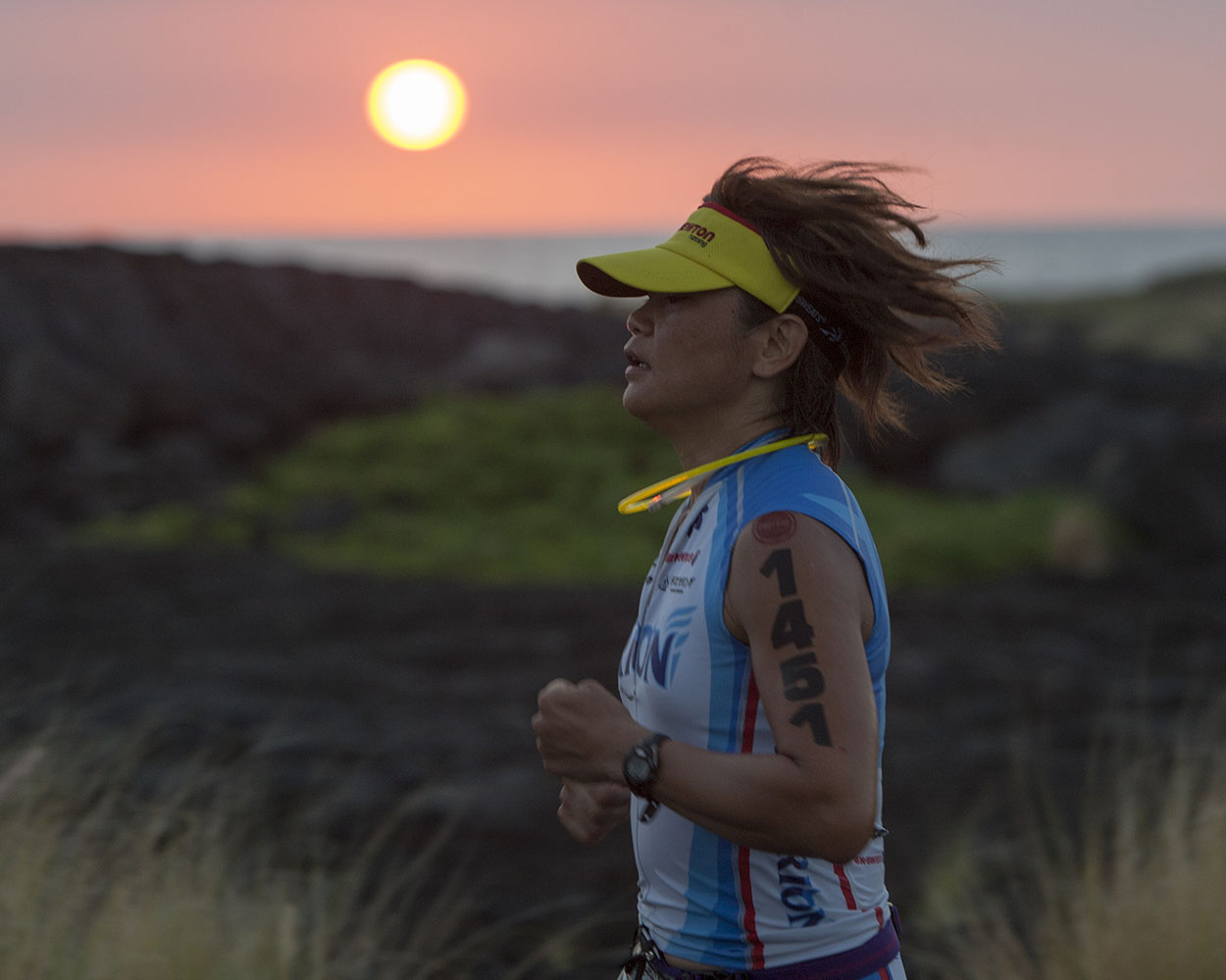 As the sun sets, Kaoru Suzuki runs the marathon during the 2014 IRONMAN World Championship.