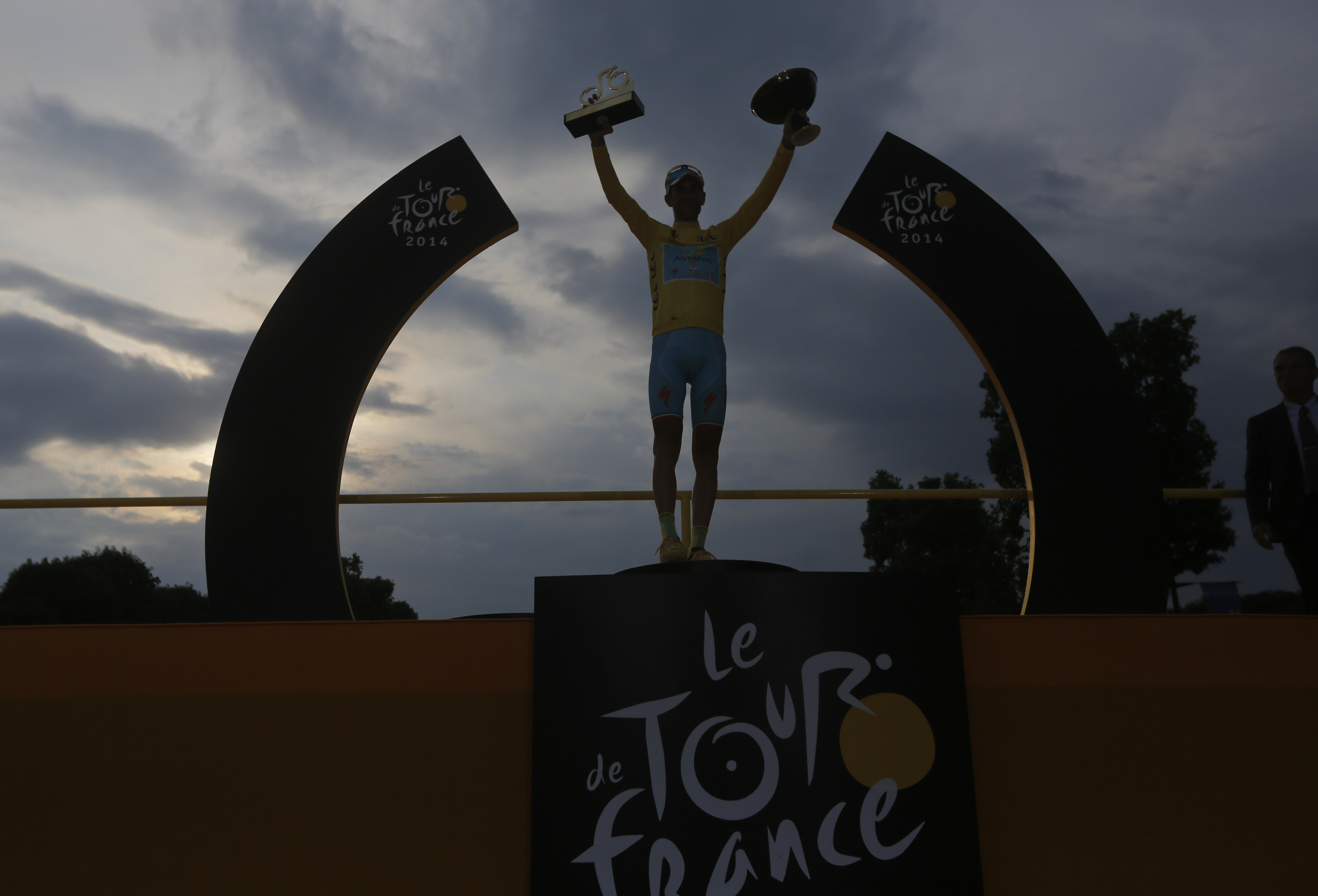 2014 Tour de France cycling race winner Italy's Vincenzo Nibali, wearing the overall leader's yellow jersey, celebrates on the podium.