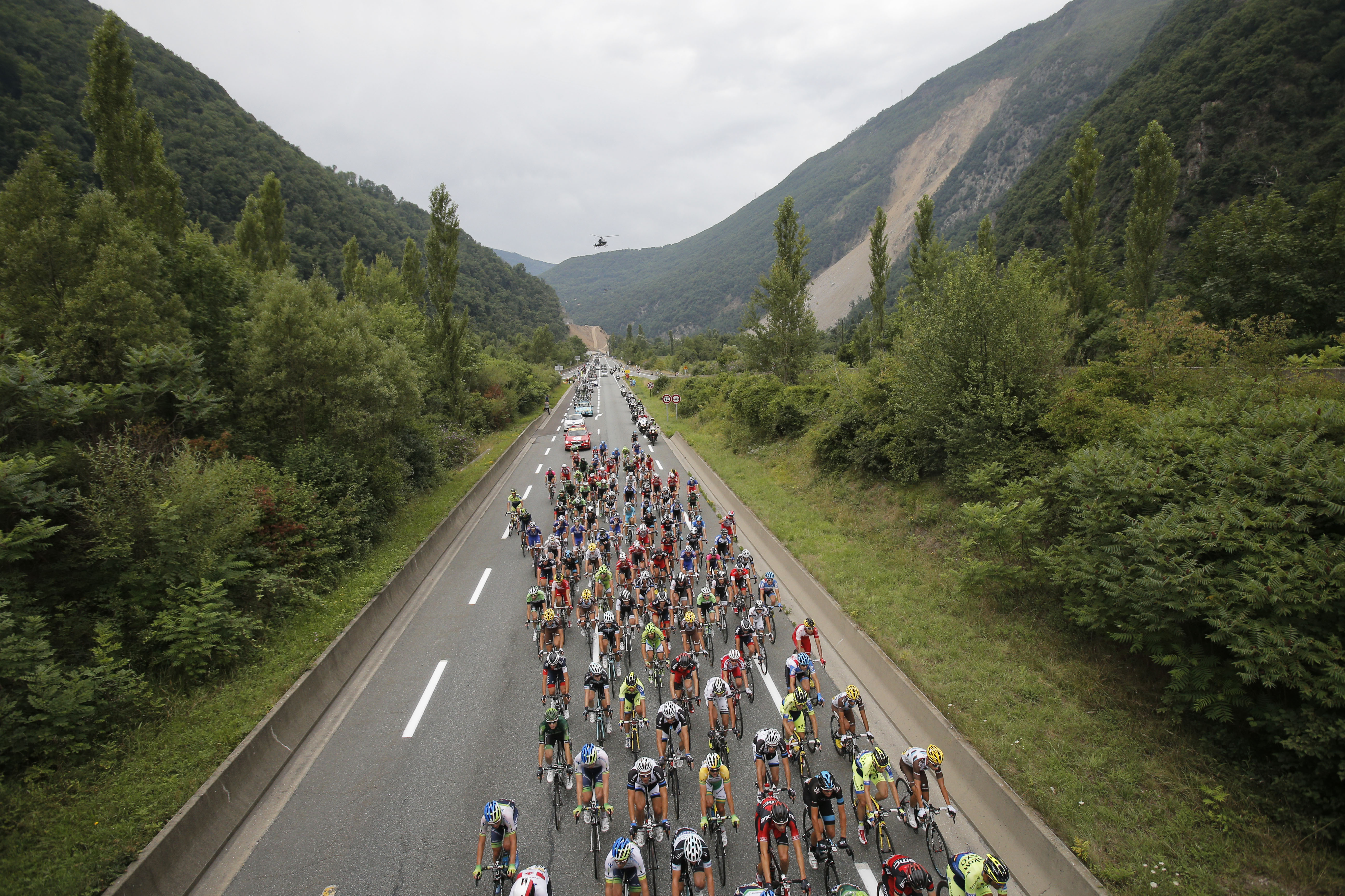 The pack passes under a bridge during the fourteenth stage of the Tour de France.