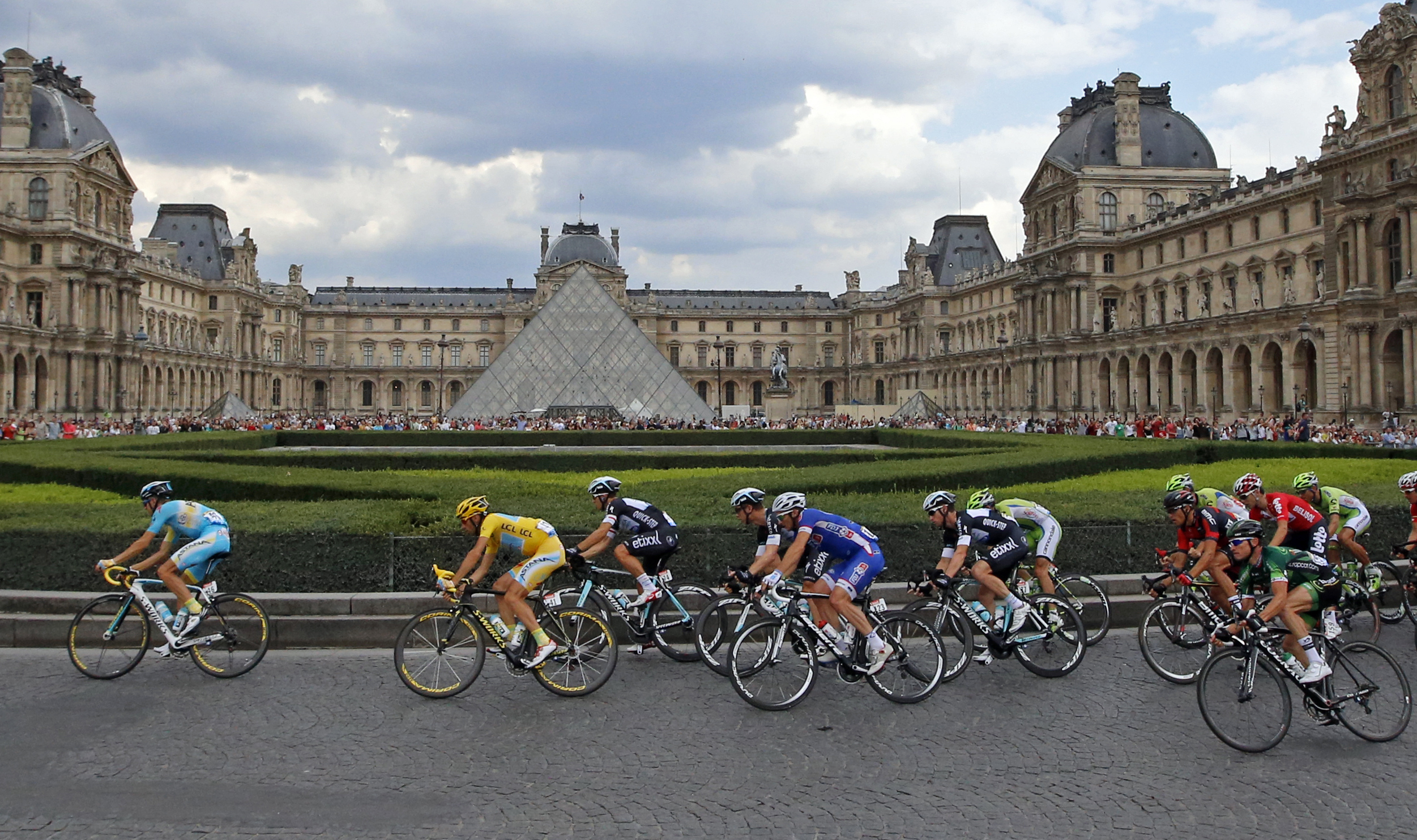 The pack, with Vincenzo Nibali of Italy, wearing the overall leader's yellow jersey, left, rides through the courtyard of the Louvre museum.