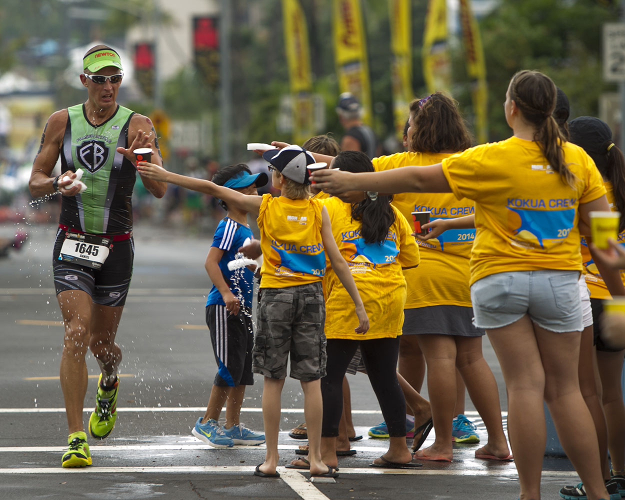Daniel Stubleski grabs water from an aid station during the marathon portion of the 2014 IRONMAN World Championship.
