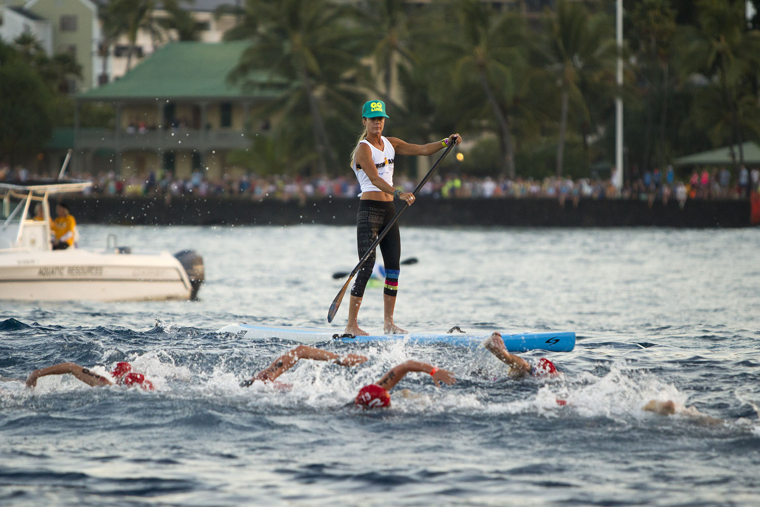 A paddle boarder watches over swimmers during the start of the 2014 IRONMAN World Championship.
