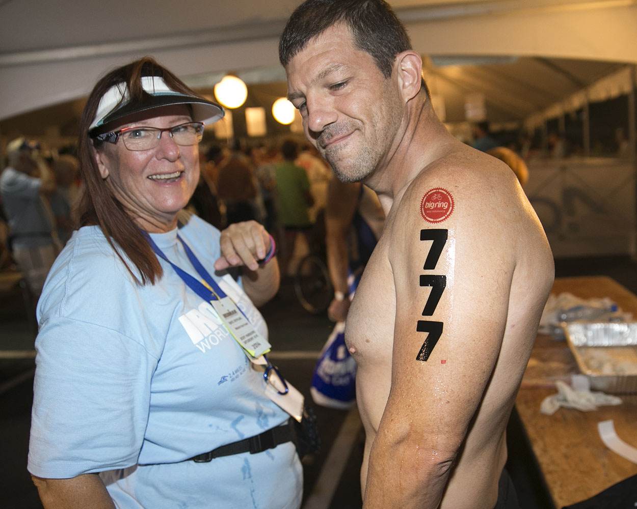 A race official places a body number on athlete Mike Avadikian before the start of the 2014 IRONMAN World Championship.