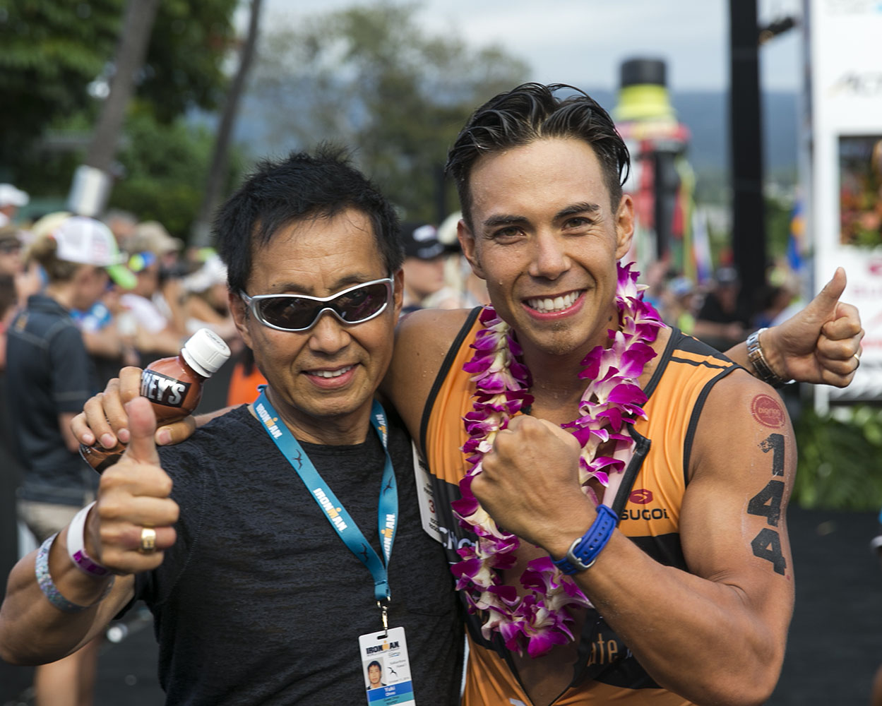 Former Olympian Apollo Ohno, right, poses with his father, Yuki Ohno after Apollo finished the 2014 IRONMAN World Championship.