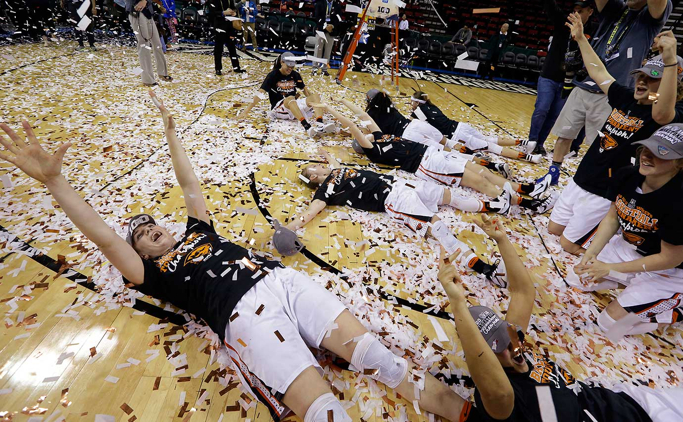 Oregon State players roll in confetti after being awarded the Pac-12 Conference tournament championship trophy in Seattle.