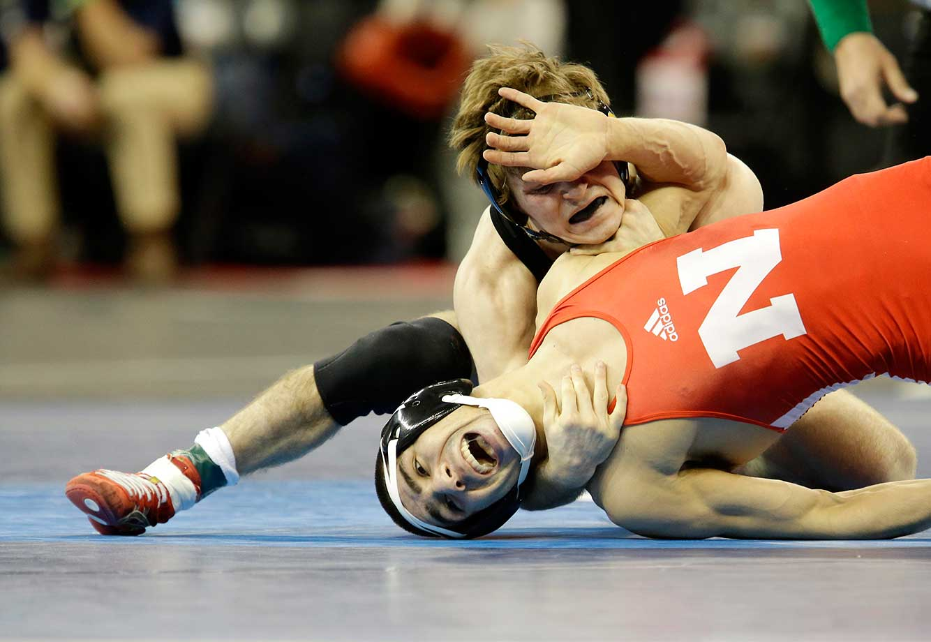 Iowa's Cory Clark, top, gets tangled up with Nebraska's Eric Montoya in a 133-pound match during the NCAA Division 1 wrestling championship in New York.