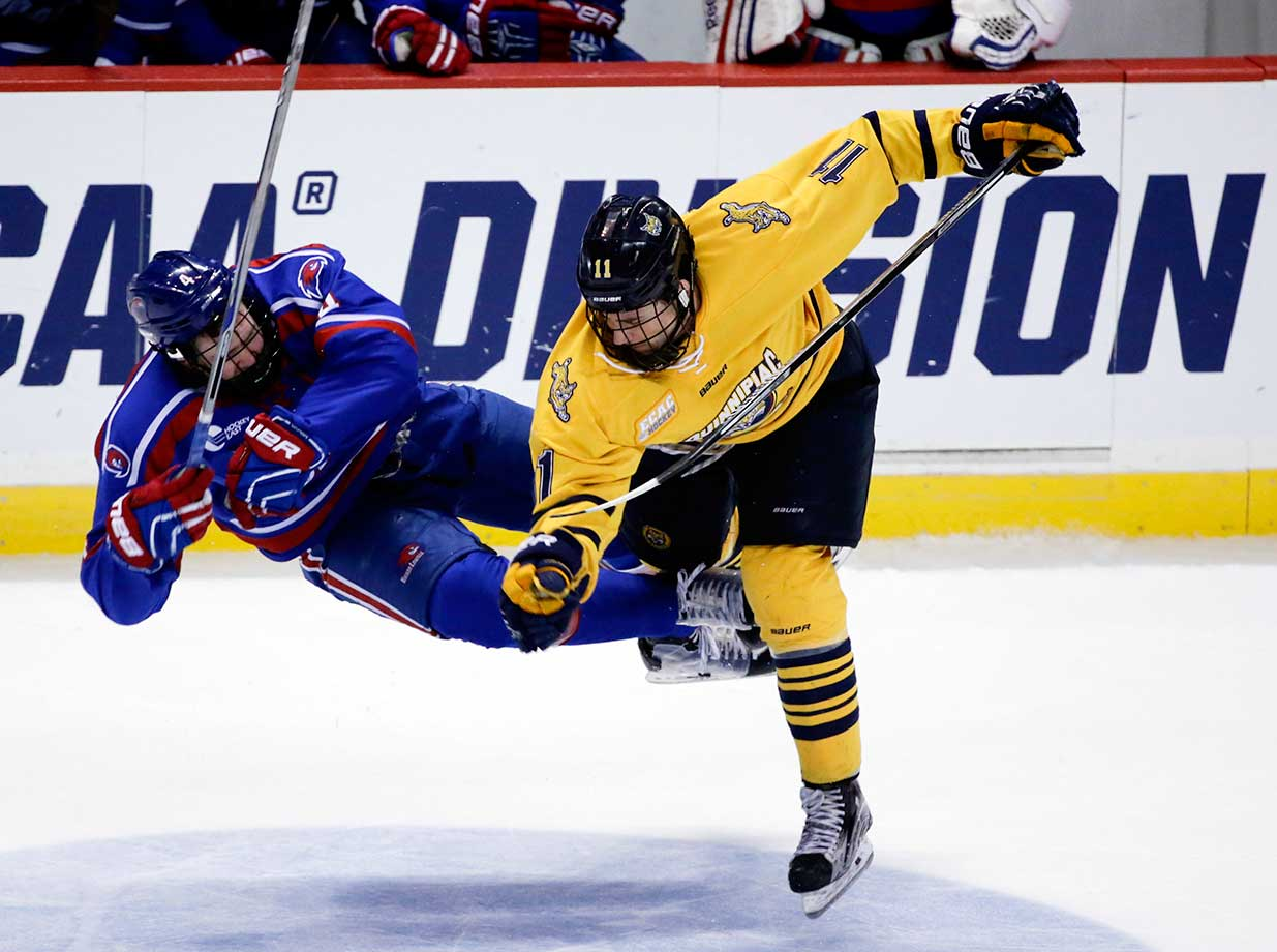 Quinnipiac's Tim Clifton hits UMass Lowell's Chris Forney during Quinnipiac's 4-1 in the NCAA East Regional championship game.