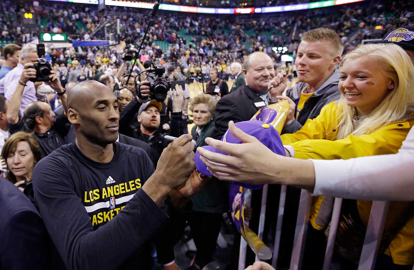 Kobe Bryant signs autographs as he leaves the court following his final game in Salt Lake City.