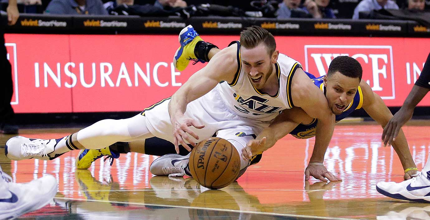 Steph Curry hits the floor with Utah forward Gordon Hayward in pursuit of the ball during Golden State's 103-96 overtiume victory. With seven games left, the Warriors (68-7) are on pace to break the 1995-96 Chicago Bulls' record of 72-10.