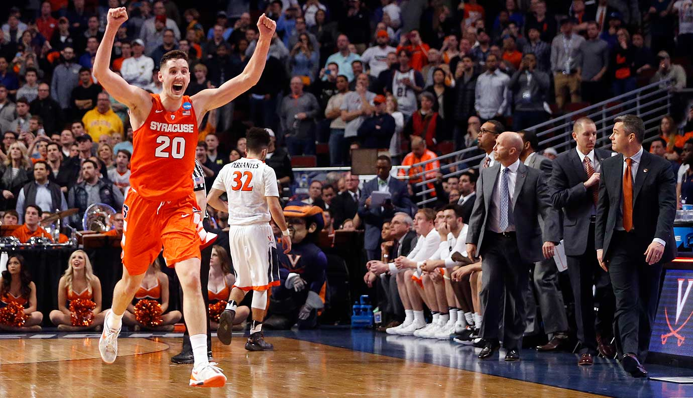 Tyler Lydon celebrates the 68-62 upset victory over Virginia while Cavs coach Tony Bennett heads to the Syracuse bench to extend his congratulations.