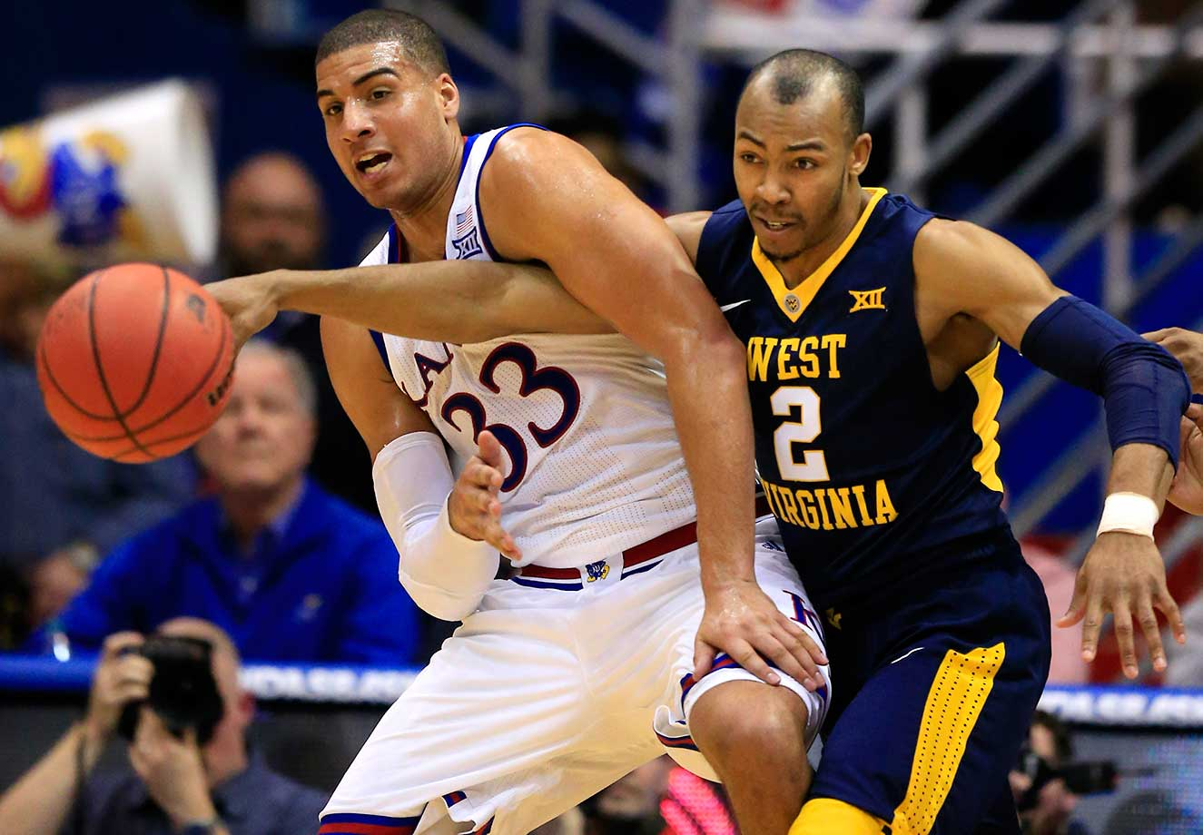 West Virginia guard Jevon Carter reaches in on Kansas forward Landen Lucas.